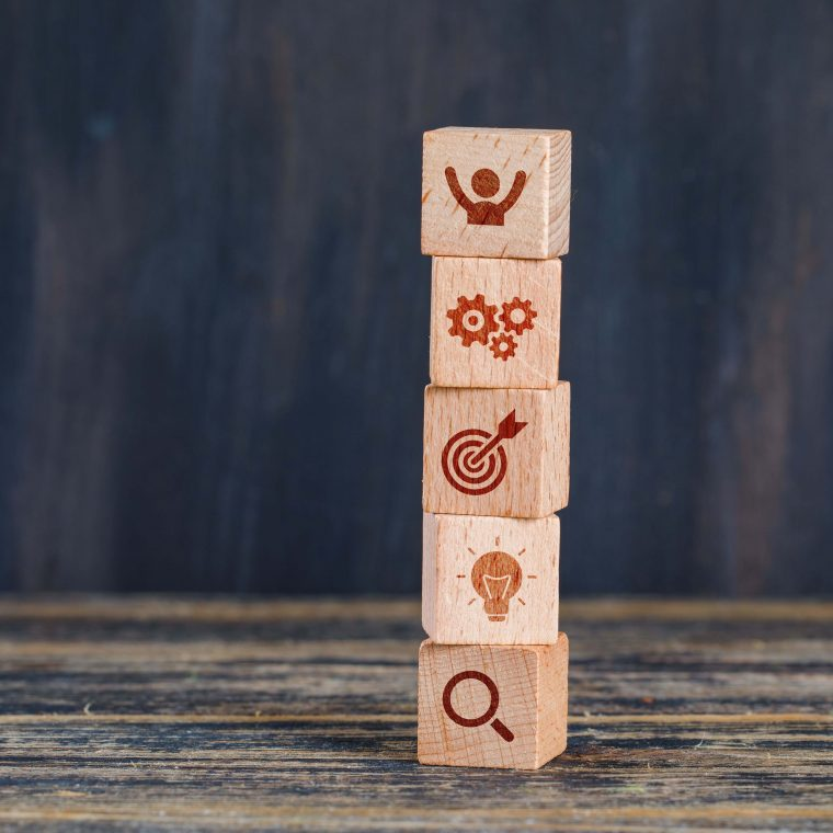 business-strategy-concept-with-wooden-cubes-on-wooden-and-grunge-background-side-view-min (1)